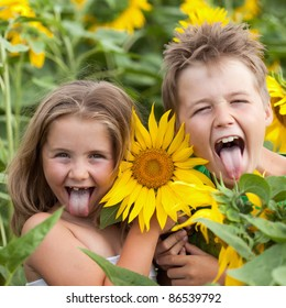 Two smiling happy children in sunflowers field shows their tongues
