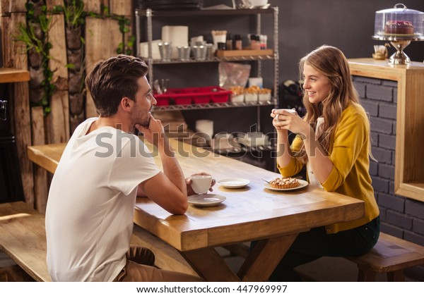 Two smiling hipsters drinking coffee at coffee shop