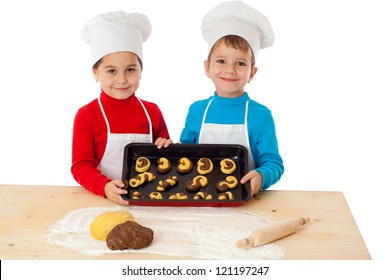 Two smiling kids with baking on oven-tray, isolated on white