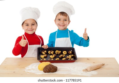 Two smiling kids with baking and thumbs up sign, isolated on white
