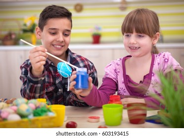 Two smiling kids paint easter eggs