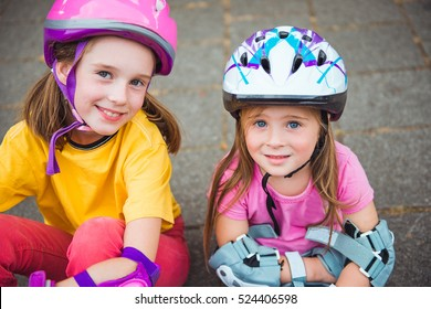 Two smiling kids in protective helmet and sportswear for cycling