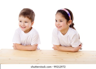 Two smiling kids sitting at the empty table and looking aside, isolated on white