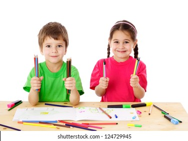 Two smiling little kids at the table with color pencils, isolated on white