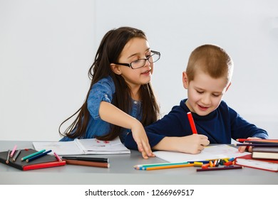 Two smiling little kids at the table draw with crayons, isolated on white