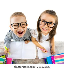 Two smiling little kids at the table in classroom at lesson. School, education concept.