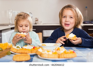Two smiling little sisters enjoying pastry with cream in kitchen at home