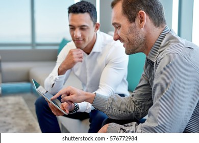 Two smiling male work coworkers sitting on a sofa in a modern office talking together over a digital tablet