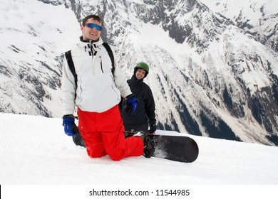 Two smiling man with snowboards on mountain
