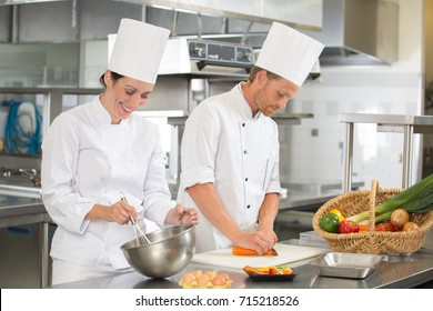 two smiling man and woman chefs cooking at restaurants kitchen