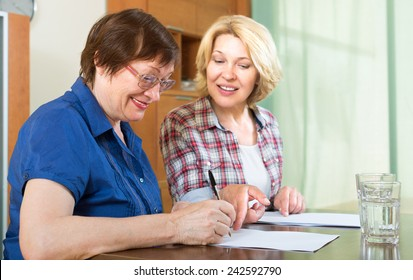 Two smiling mature woman sitting at the table and signing contracts