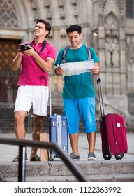 Two smiling men with suitcases are walking with map and photographing in Barcelona.