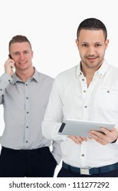 Two smiling men using phone and tablet computer against a white background