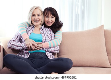 Two smiling middle aged women, talking at home