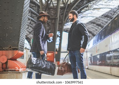 Two smiling multi-ethnic bearded businessmans together wearing casual clothes and holding travel bags in hands waiting the train on the railway platform.