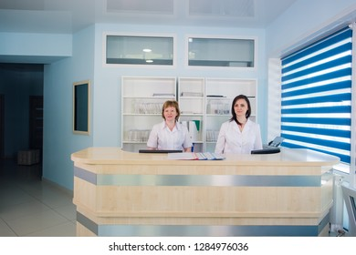 Two smiling nurses working at hospital reception desk
