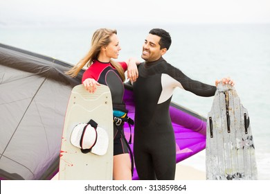 Two smiling people with kiteboardon at the beach