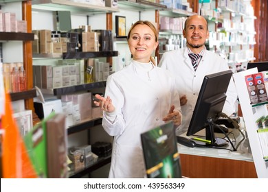 Two  smiling pharmacists standing with a cash desk in the pharmacy