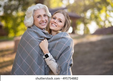 Two smiling relaxed women standing on a park.