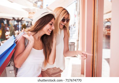 Two smiling shopaholic women enjoying in shopping, having fun together in the city. Consumerism, fashion, lifestyle concept