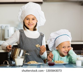 Two smiling small girls eating healthy oatmeal at home kitchen