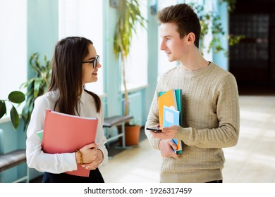 Two smiling students in love communicate during break holding learning materials afraid to express their feelings to one another