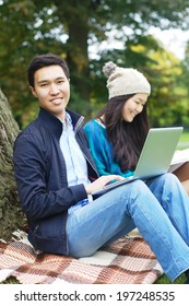 Two smiling students revising at the park
