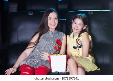 two smiling teen girls sitting at the cinema, watching a film and eating popcorn. movie theater.