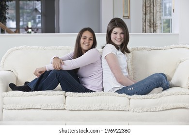 Two smiling teenage girlfriends sitting back to back on a white sofa at home