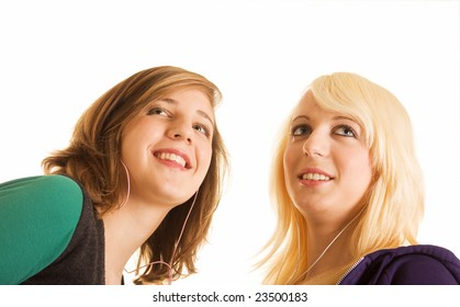 Two smiling teenager girls listening their music players