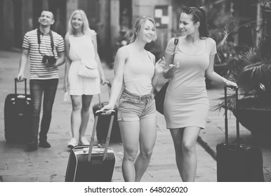 Two smiling traveling girls walking together with luggage and looking around in city