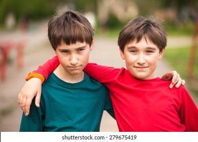Two smiling twin brothers outdoor portrait