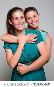 Two Smiling Twin Sisters Hugging