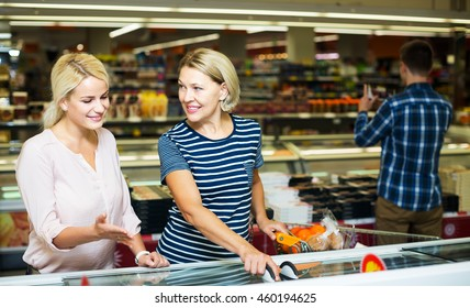 Two smiling women buying frozen vegetables in grocery store. Focus on mature woman