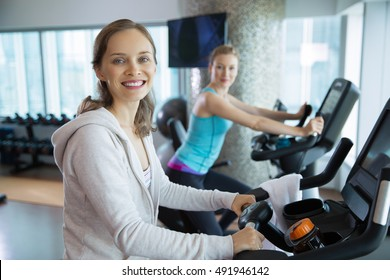 Two smiling women cycling on exercise bikes in gym