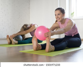 Two smiling women doing stretching head to knee with small fit balls in fitness studio, selective focus. Yoga, workout, pilates, good mood, exercise therapy, flexibility, sport, activity and physical