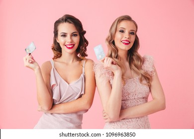 Two Smiling women in dresses posing together while holding credit cards and looking at the camera over pink background