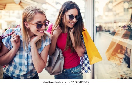 Two smiling women enjoying in shopping, having fun together in the city. Consumerism, fashion, lifestyle concept