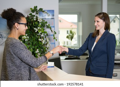 Two smiling women greet each other with handshake over a counter in the office.