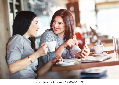 Two smiling women have coffee time