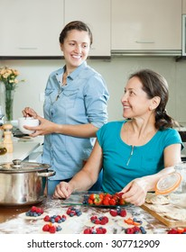 Two smiling women making  vareniki with berries together at home kitchen