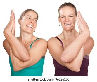 Two smiling women in Namaskar pose with twisted hands