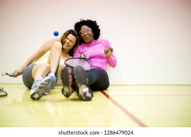 Two smiling women sitting together on a racquetball court.