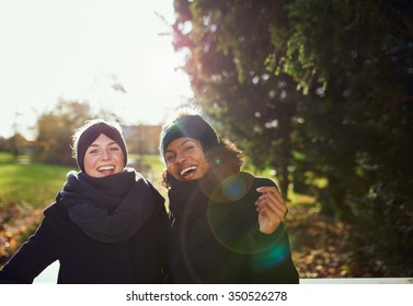 Two smiling women standing on bridge in park.Sunny
