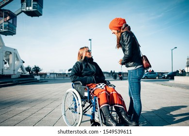 two smiling women talking and spending time together outdoor in the city - sitting on a wheelchair and living a disability with positive attitude concept