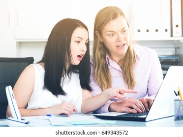 Two smiling women workers working effectively on project in office