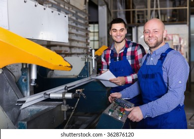 Two smiling workers posing in PVC shop indoor