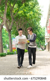 Two smiling young businessmen walking and talking in the city