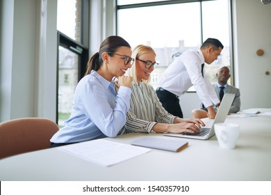 Two smiling young businesswoman working together on a laptop while sitting at a boardroom table with colleagues in the background