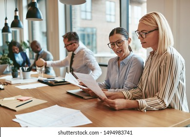 Two smiling young businesswomen reading paperwork together while sitting at a boardroom table during an office meeting